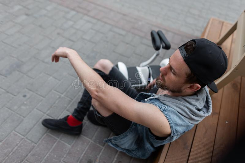 American modern young man in a trendy cap in a denim vest in stylish black ripped jeans in sneakers sits next to a hoverboard stock photos