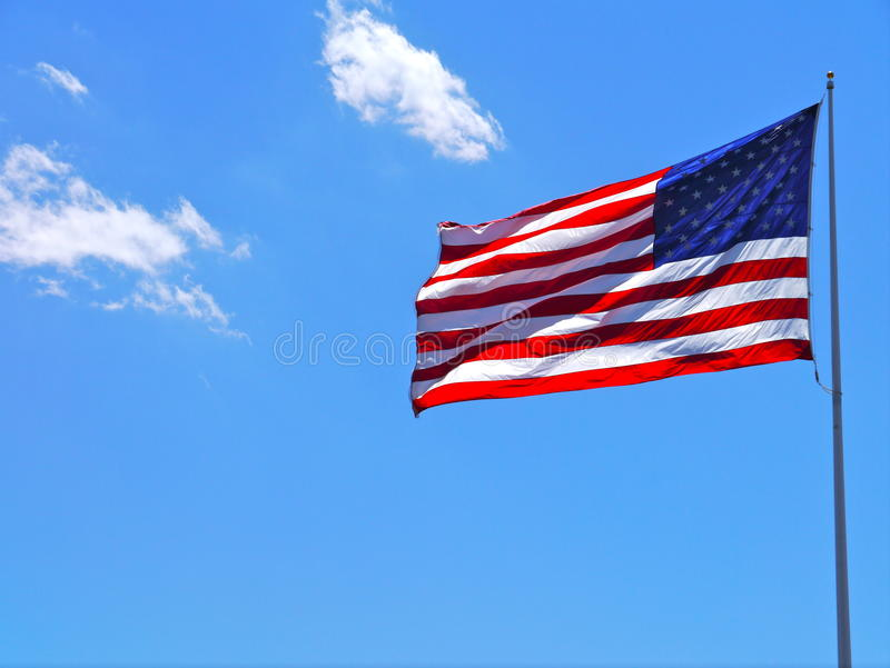 American national flag. The Star Spangled Banner flying at the top of a flagpole against blue sky stock photos