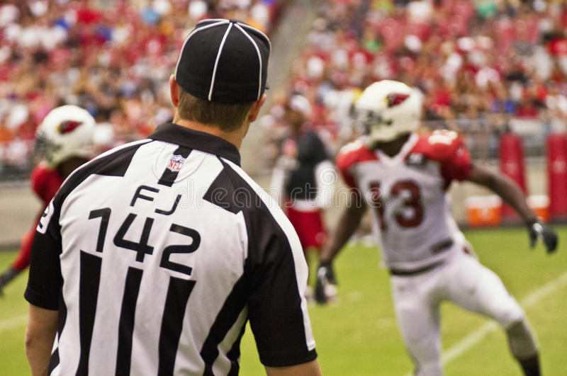 American NFL Football Field Judge Official. An American NFL field judge official looks on as professional NFL football players play in a favorite American stock photography