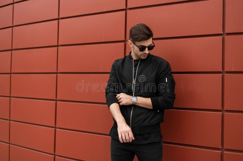 American nice young hipster man in a fashionable jacket in stylish sunglasses with trendy hairstyle walks in the city. On a summer day. Modern guy model near royalty free stock photos