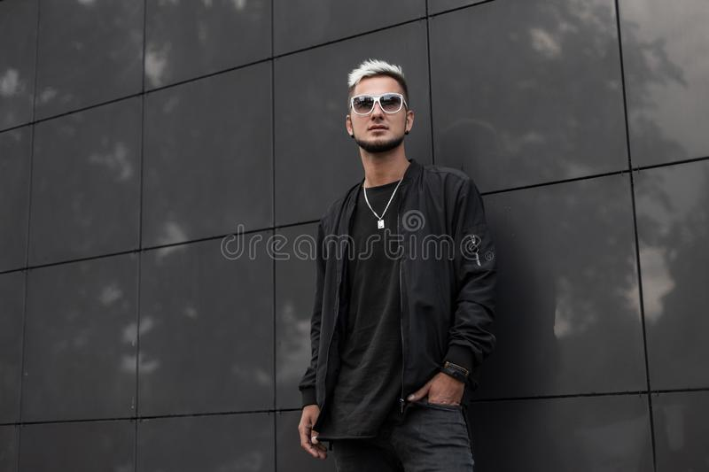 American nice young hipster man in a fashionable jacket in stylish sunglasses with trendy hairstyle walks in the city. On a summer day. Modern guy model near stock photos
