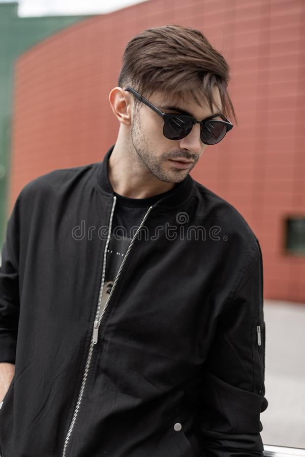 American nice young hipster man in a fashionable jacket in stylish sunglasses with trendy hairstyle walks in the city. On a summer day. Handsome guy model near stock photos