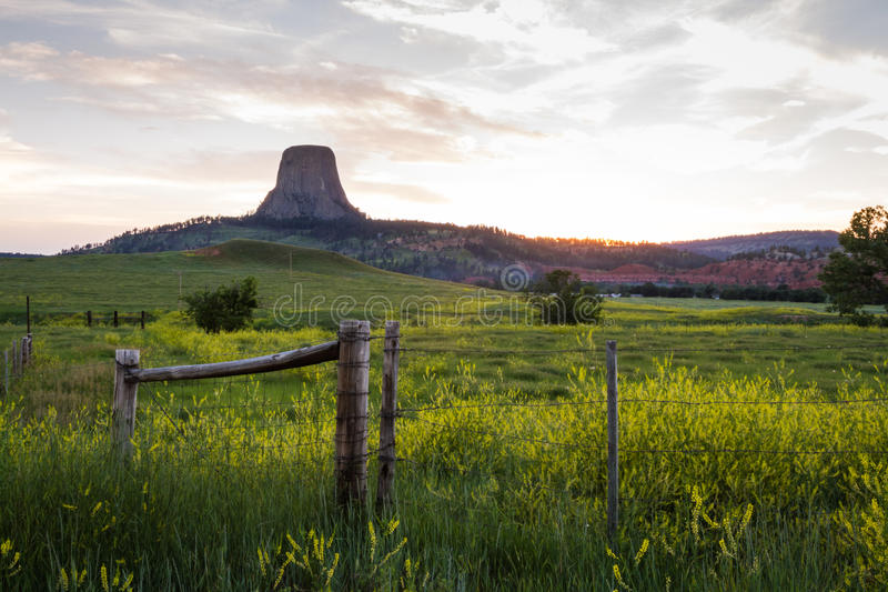 The American old west. Sunset including a farm and Devils Tower National monument , old west concept royalty free stock image