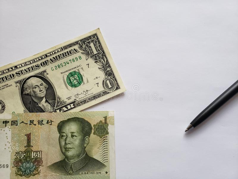 American one dollar bill, chinese banknote of one yuan, black pen and white background. Chinese, banknotes, american, dollar, backdrop, announcements, trading stock photo
