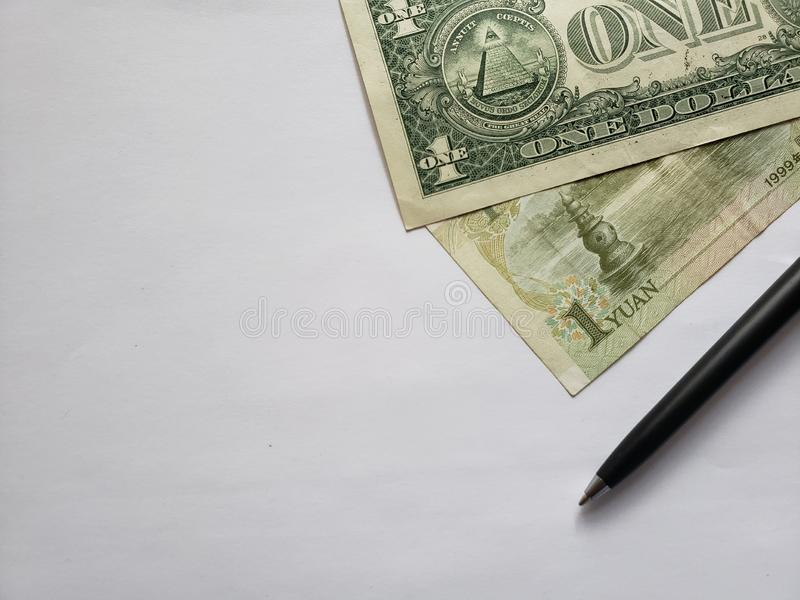 American one dollar bill, chinese banknote of one yuan, black pen and white background. Chinese, banknotes, american, dollar, backdrop, announcements, trading royalty free stock photo