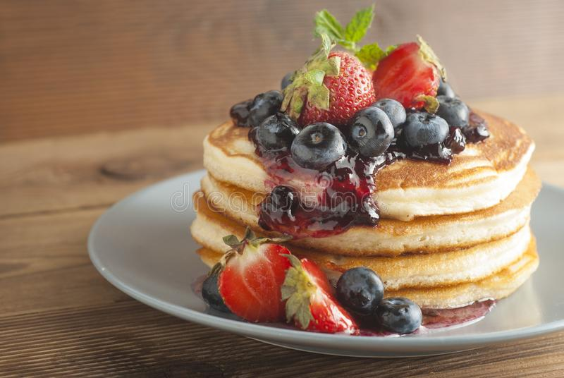 American pancakes or fritters served with strawberry and blueberry jam, delicious dessert for breakfast, rustic style, wooden back stock photo