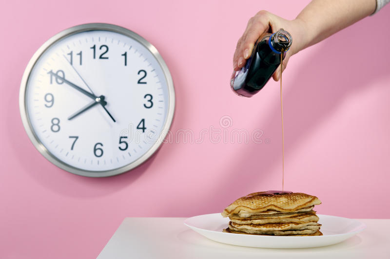 American pancakes with maple syrup poured. In the background the clock on a pink wall royalty free stock images