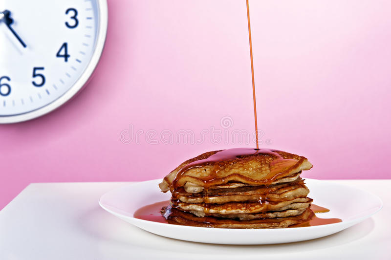 American pancakes with maple syrup poured. In the background the clock on a pink wall royalty free stock image