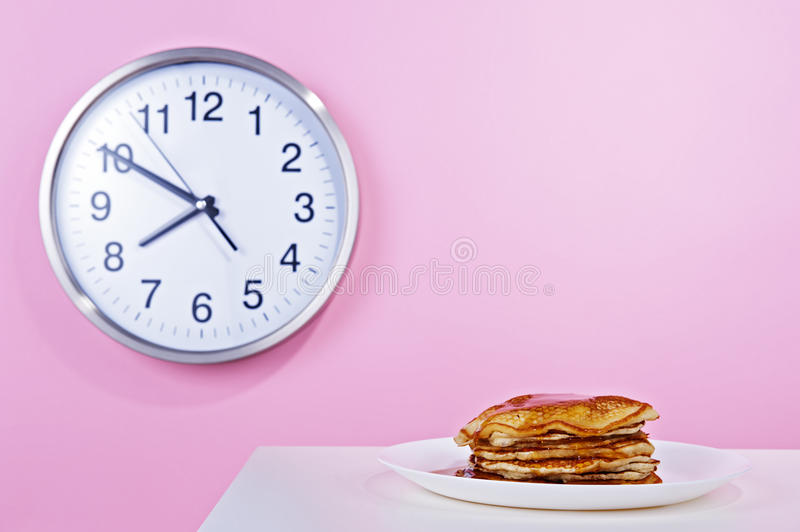 American pancakes with maple syrup poured. In the background the clock on a pink wall stock images