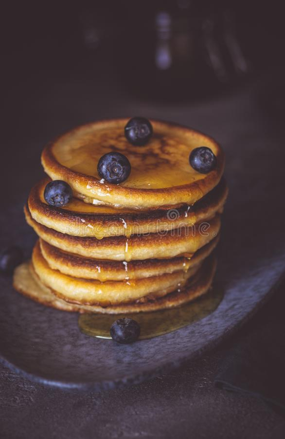 American Pancakes with Organic Berries and Maple Syrup on Dark Background. Classic Homemade Breakfast. stock photos