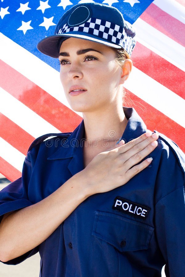 American policewoman. Portrait of caucasian American policewoman pledging allegiance with USA flag as background royalty free stock images