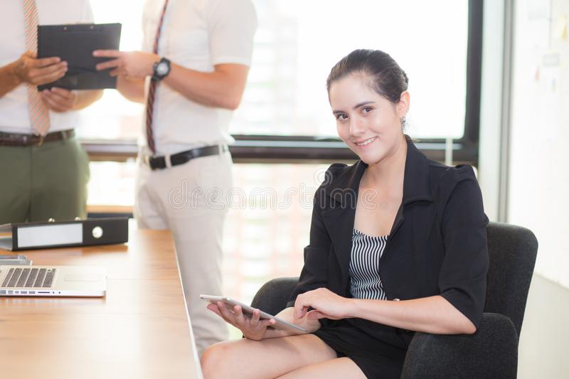American portrait of businesswoman sitting in modern office business people background. stock images