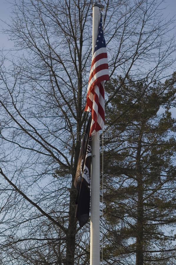 American and POW flag displayed against winter trees. An American flag with the POW flag hanging limp on a flag pole stock photos