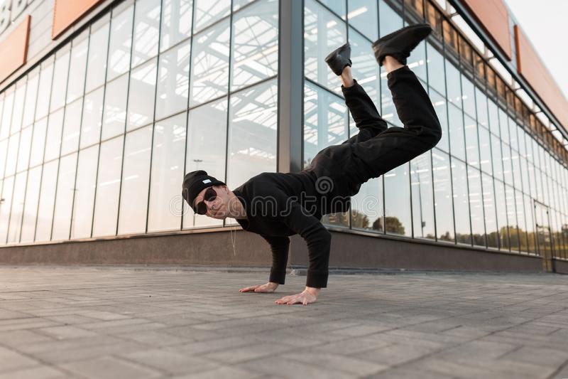 American pretty young hipster man in stylish black clothes in a fashionable knitted hat in leather sneakers poses. Near a modern glass building. Handsome guy royalty free stock images