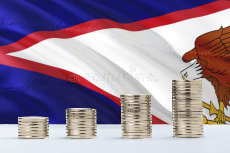 American Samoa flag waving in the background with rows of coins for finance and business concept. Saving money stock photography
