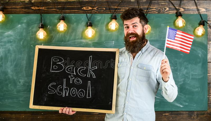 American school concept. Teacher holds blackboard with written phrase back to school and flag of USA. Man with beard on royalty free stock images
