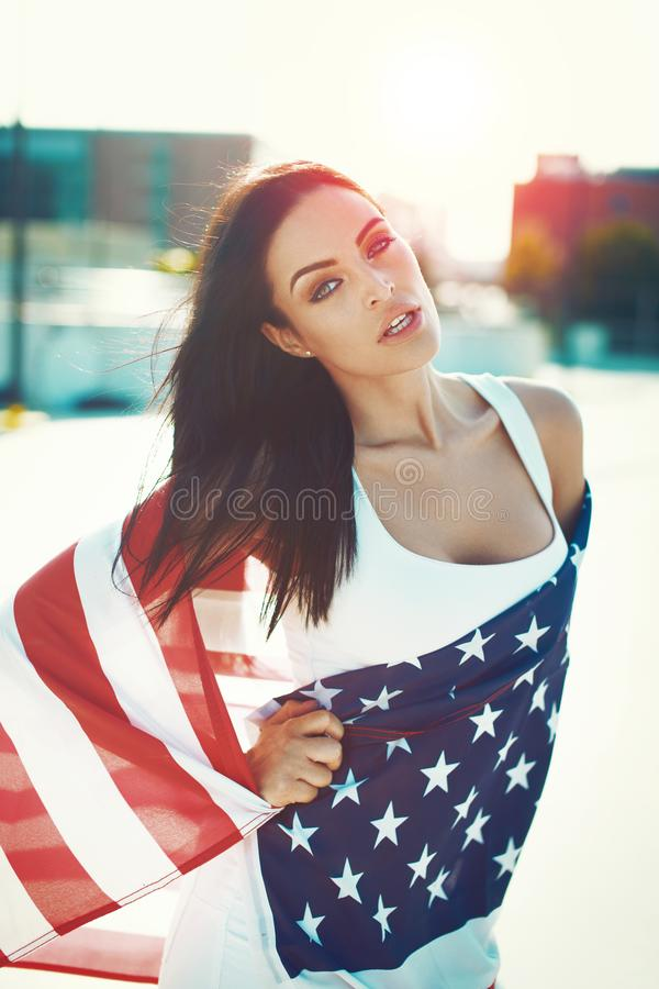 American sensual beauty covered by star spangled banner in sunset. American beauty covered by star spangled banner in sunset, looking into camera, Independence stock photo