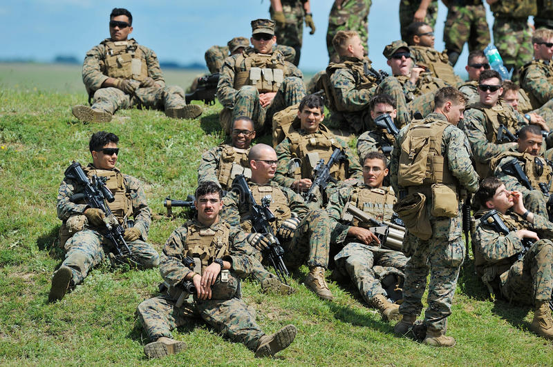 GALATI, ROMANIA - MAY 15, 2015: American and Serbian soldiers rest after a shooting session in the polygon, in Galati, Romania, m royalty free stock photography