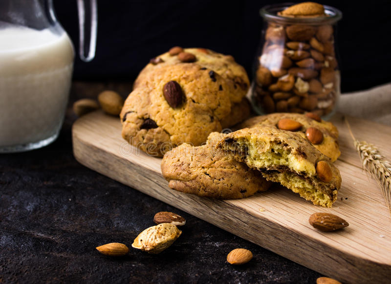 American shortbread cookies with chocolate drops and a jug of milk and almonds. Dark grunge background. Mystical light royalty free stock photography