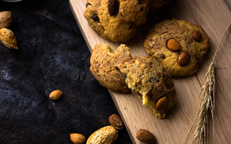 American shortbread cookies with chocolate drops and a jug of milk and almonds. Dark grunge background. Mystical light royalty free stock images