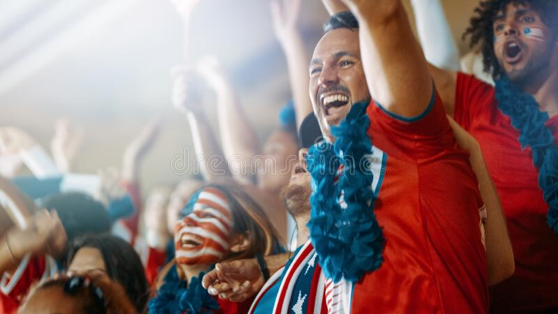 American soccer fans cheering their team in stadium. Excited USA football fans and supporters celebrating a goal being scored in the sports stadium. American stock photography
