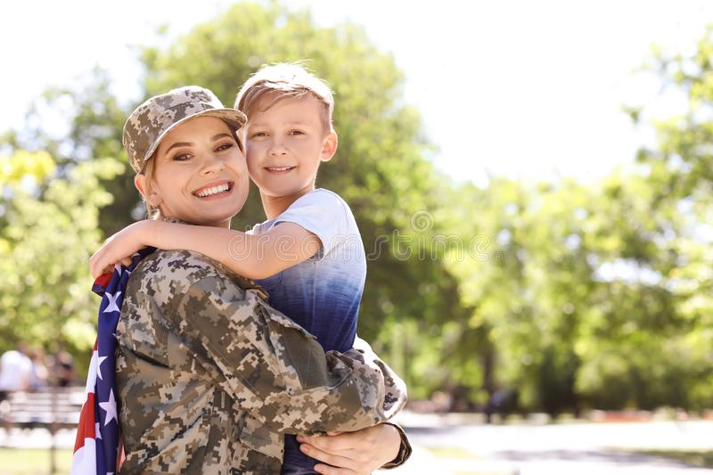 American soldier with her son outdoors. Military service royalty free stock photo