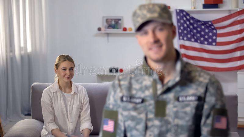 American soldier smiling at camera, proud wife sitting on sofa against US flag. Stock photo royalty free stock photo