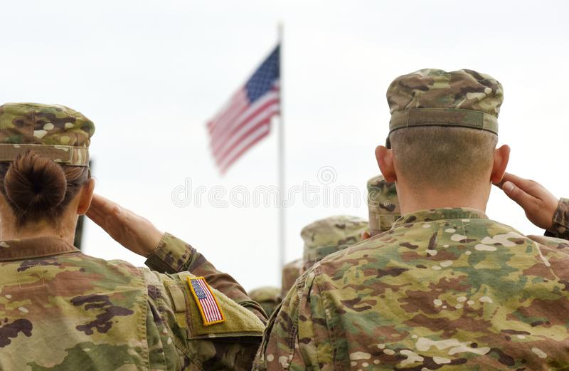 American Soldiers Saluting US Flag.  stock photo