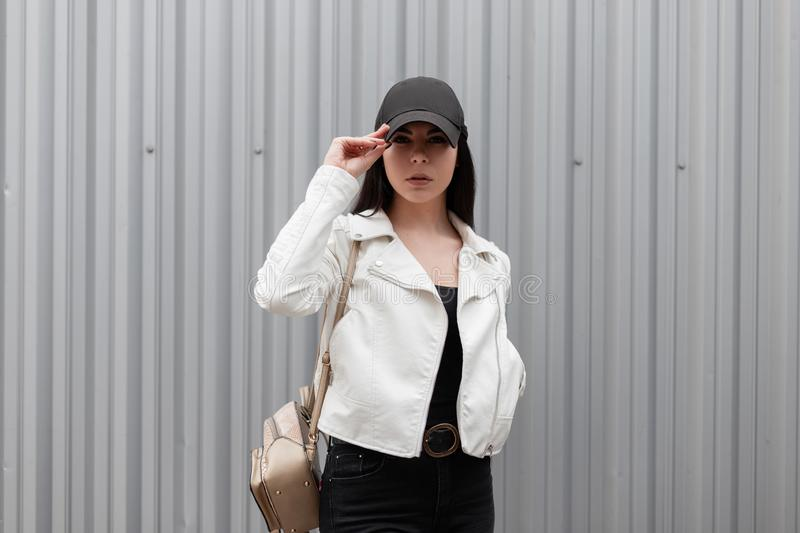 American stylish young woman in a trendy black baseball cap in a leather white jacket in black jeans with a gold backpack stock image