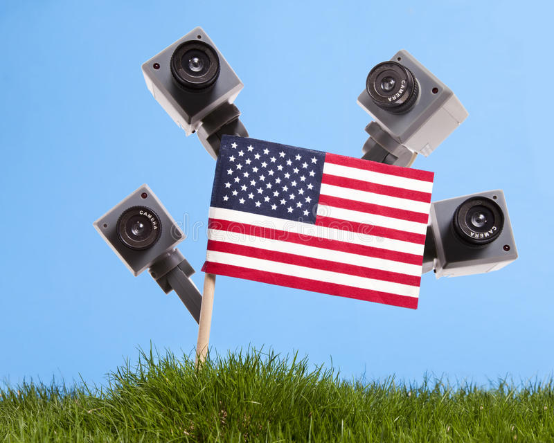 American Surveillance. Several security cameras peek out from behind an American Flag stock photo