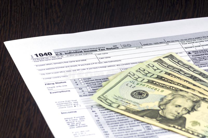 American Tax form 1040 is on the table. A few bills are on top. Cash of 20 and 100 dollars. American Tax form 1040 is on the table. A few bills are on top. Cash royalty free stock photo