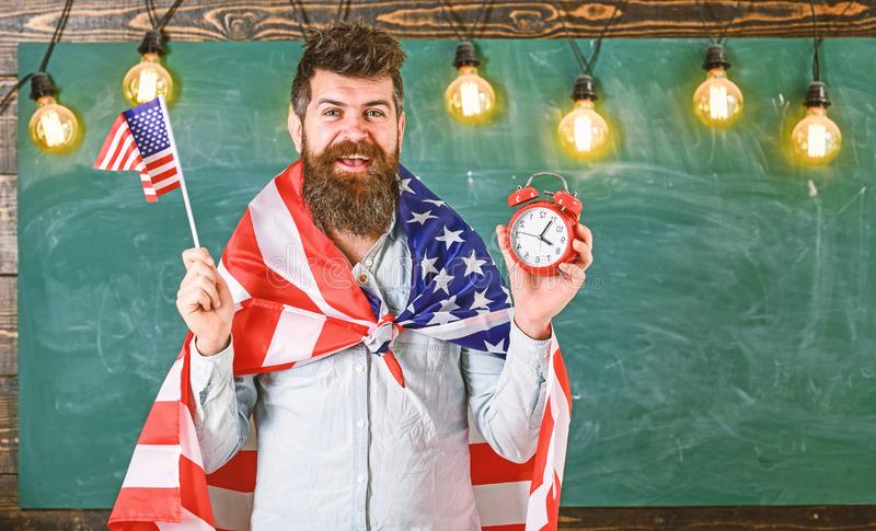 American teacher with american flags holds alarm clock. Man with beard on cheerful face holds flag of USA and clock. Chalkboard on background. American stock photo
