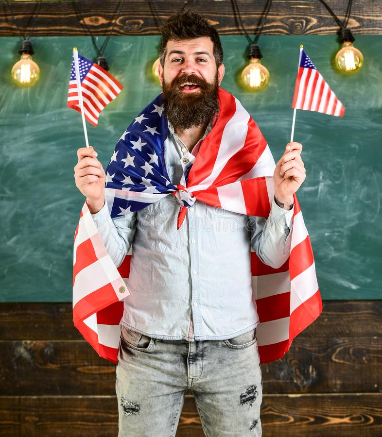 American teacher waves with american flags. Student exchange program. Patriotic education concept. Man with beard and stock photo