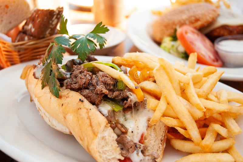 American beef cheese steak sub sandwich and fries on white plat. American tender beef cheese steak sub sandwich and fries on white plate royalty free stock image