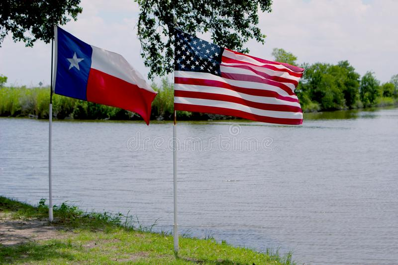 American and Texas Flag Waving in front of River stock photos