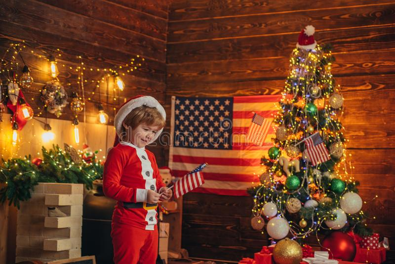 American traditions concept. Cute baby toddler celebrate christmas. American child cheerful mood waving flag. Kid play. American flag christmas tree. Little boy stock image