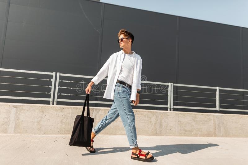 American trendy young man in stylish clothes in red sandals with a fabric bag in sunglasses is traveling on the street. Near the gray building. Stylish guy stock images