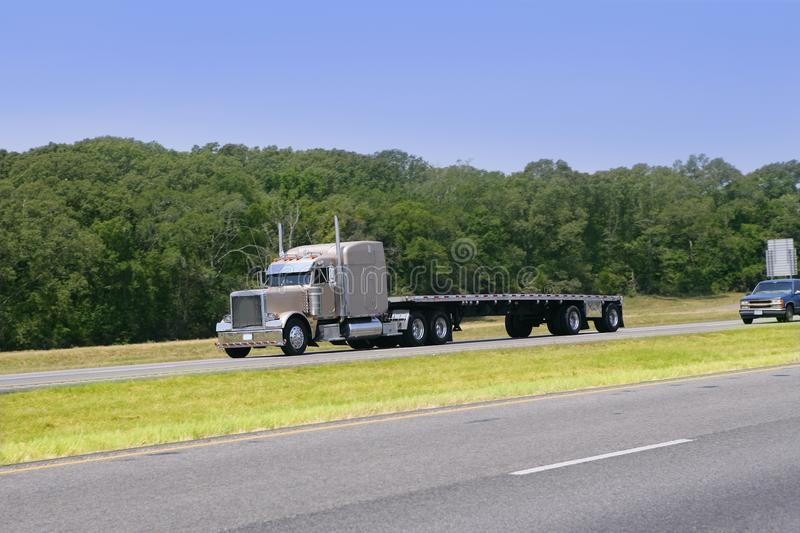 American Truck driving on a road. With green forest stock photo
