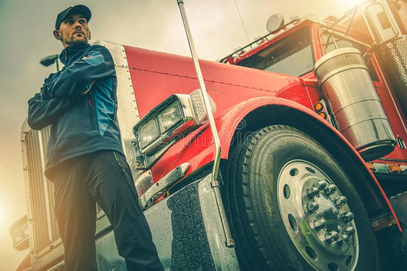 American Trucker Job. Caucasian Truck Driver in Front of His Red Semi Truck royalty free stock photography