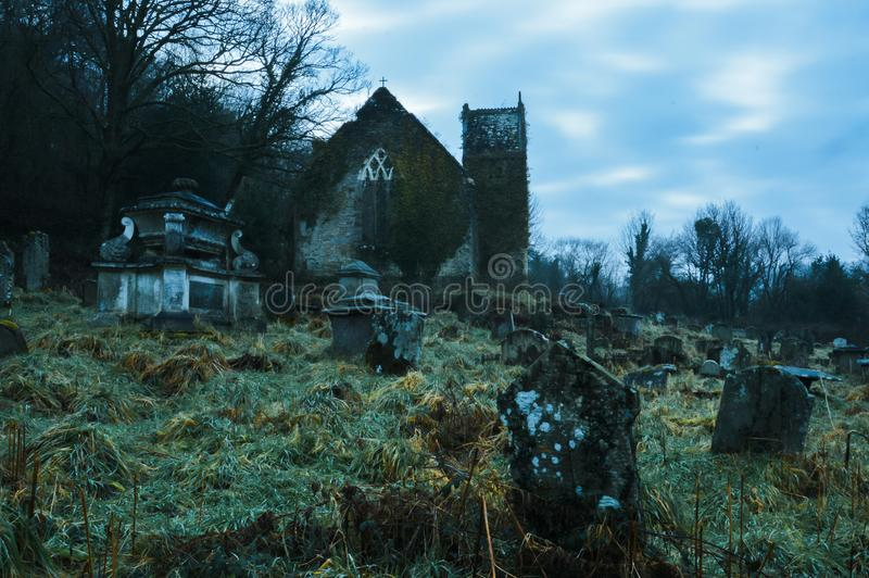 The American and UK flags imposed over containers representing trade between the two countries. A spooky, eerie, abandoned graveyard with a ruined church in the stock photo