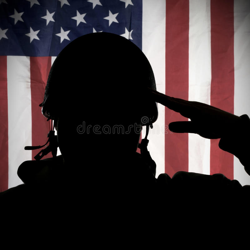 American (USA) soldier saluting to USA flag. In uniform and helmet royalty free stock images