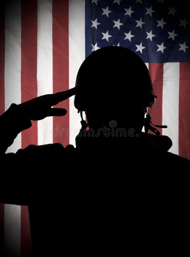 American (USA) soldier saluting to USA flag. American (USA) soldier or veteran in uniform and helmet saluting to USA flag royalty free stock images