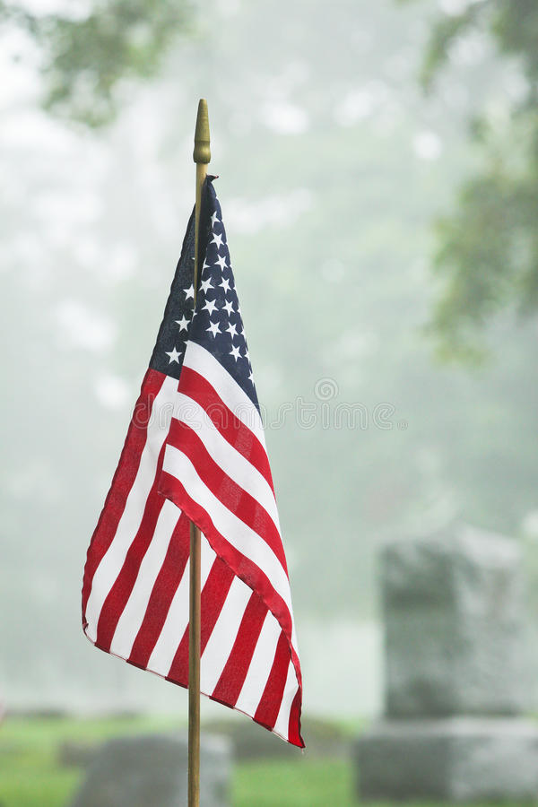 American veteran flag in foggy cemetery stock image
