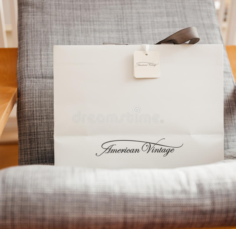 American Vintage shopping bag on armchair. PARIS; FRANCE - OCT 24; 2016: White shopping bag with AMERICAN VINTAGE fashion brand logotype on the armchair royalty free stock photo