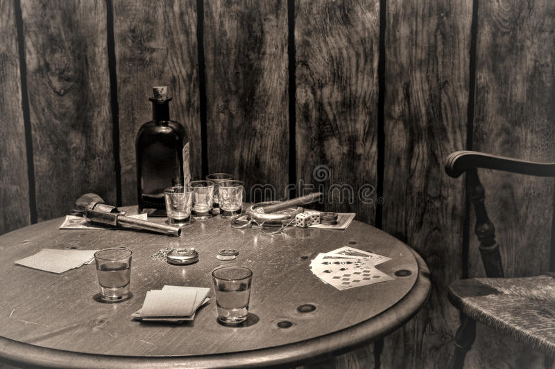 American West Legend Antique Saloon Gambling Table. American West legend antique saloon gambling wood table with vintage poker playing cards and old whisky shot stock image