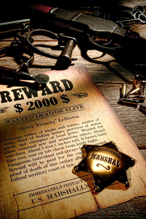 American West Legend Marshall Badge and Old Reward. American West Legend United States Marshall lawman antique brass star badge on old wanted reward fugitive royalty free stock photo