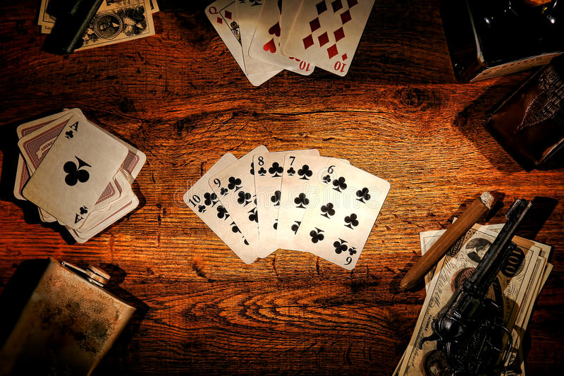 American West Poker Game Straight Flush in Saloon. American West legend old gambler poker game with playing cards showing a straight flush hand on a wood table royalty free stock photography