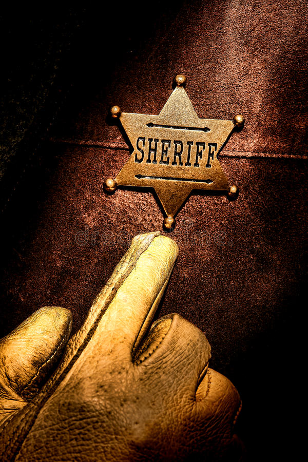 American West Legend Sheriff Badge Finger Pointing. American West Legend lawman pointing with his finger and hand wearing an old western glove to his sheriff royalty free stock photo