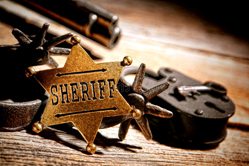 American West Legend Sheriff Badge Star and Tools. American West legend sheriff star badge lawman medallion with tools of the trade vintage western spurs and royalty free stock photos