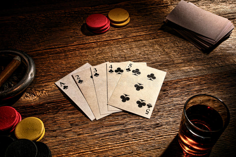 American West Old Saloon Poker Game Straight Flush. American West legend old gambler poker game with vintage playing cards showing a steel wheel or five high stock image